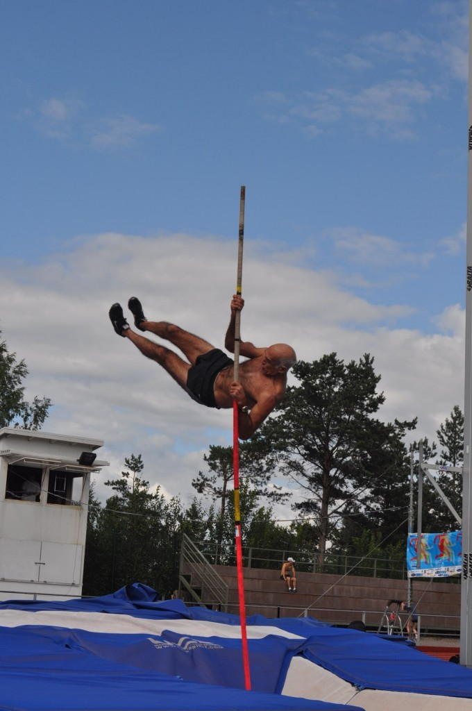 75 year old shirtless man doing the pole vault in the decathlon