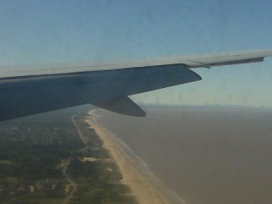 Wing of a plane, coastline of Montevideo through airplane window, sky.