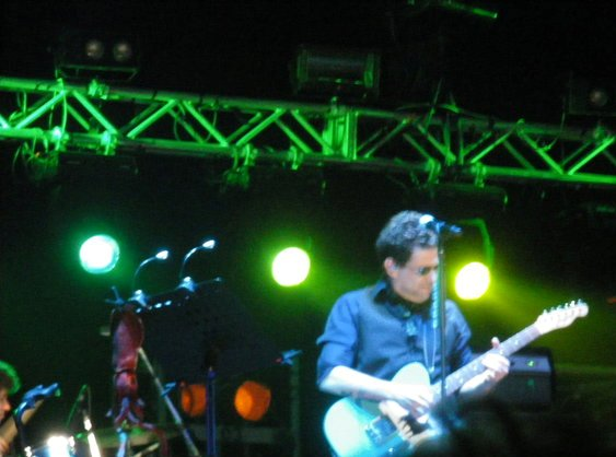 Calamaro on stage with guitar and squid amulet