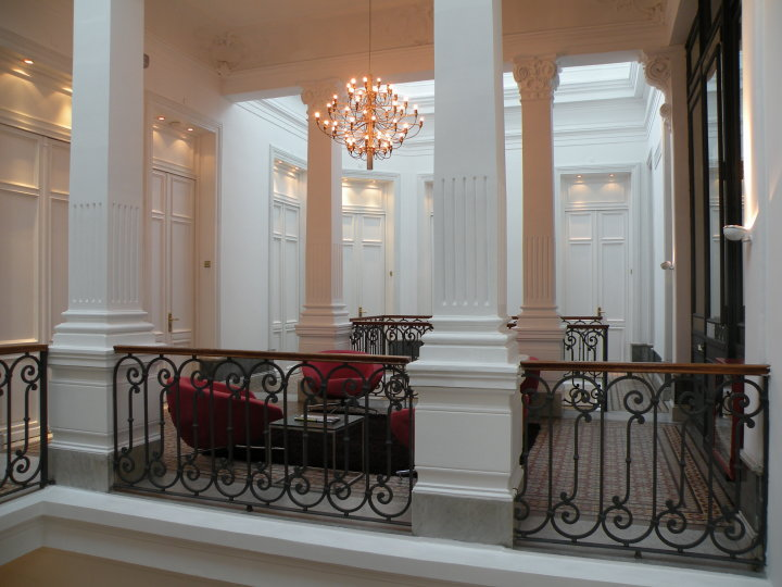 A majestic hall with columns in white with red furniture at Plaza Fuerte hotel Montevideo