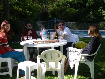 lunch table out in a garden, four people eating