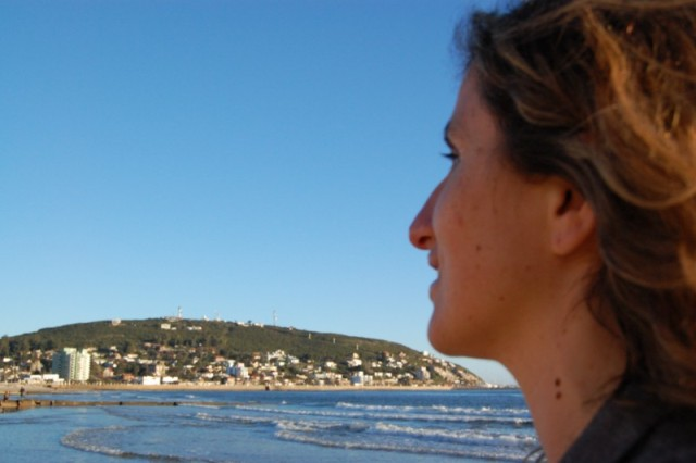 Girl looking at hill across the sea, Piriapolis, Uruguay