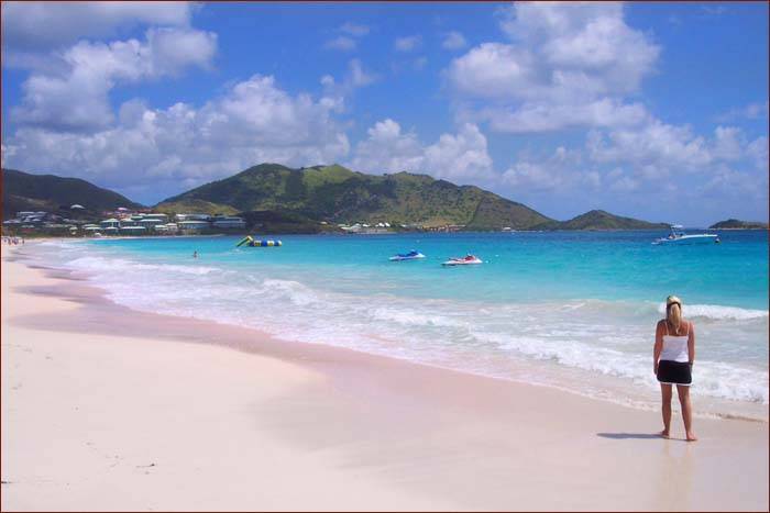 Orient beach in St. Maarten. Blue waters, hill in the background, white sands.